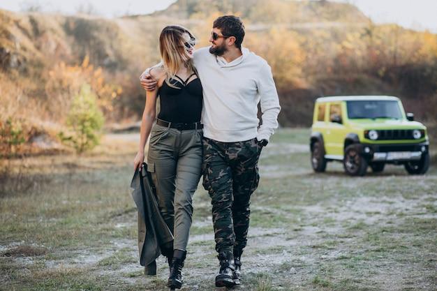 Jeune couple voyageant en voiture, arrêté pour une promenade dans le parc