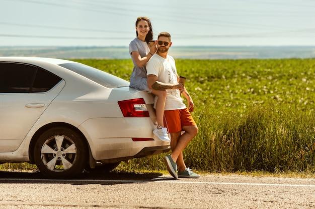Jeune couple voyageant sur la voiture en journée ensoleillée