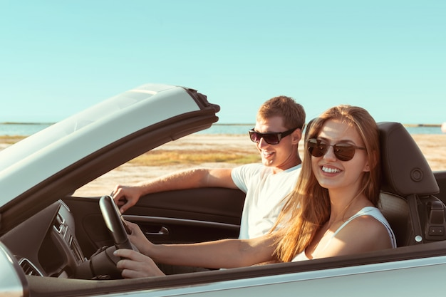 Jeune couple voyageant en voiture
