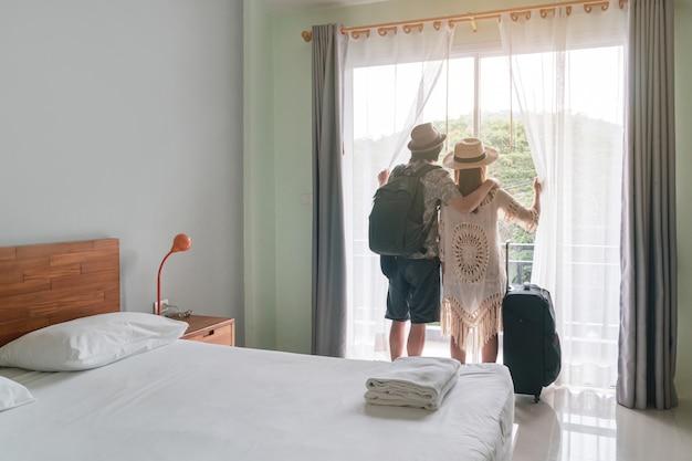 Jeune couple voyageur avec bagages en regardant la vue dans la chambre d'hôtel en vacances d'été