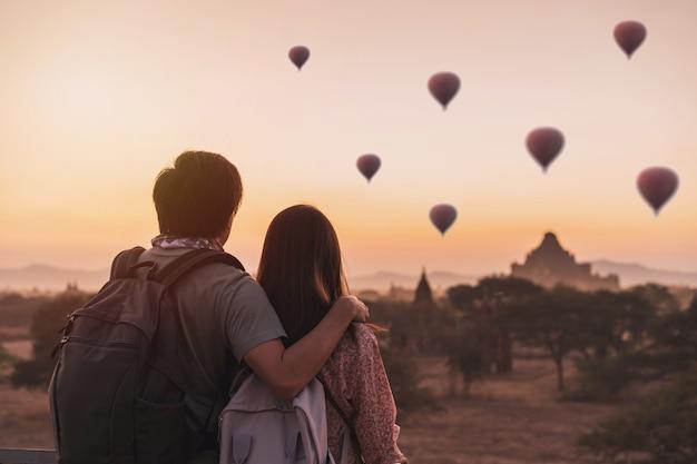 Jeune couple voyageur profitant de ballons sur l'ancienne pagode à bagan, myanmar au lever du soleil