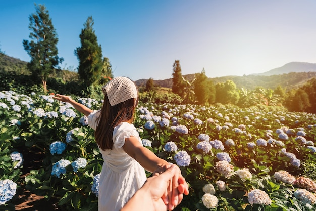 Jeune couple voyageur se détendre et profiter avec champ de fleurs d'hortensias en fleurs