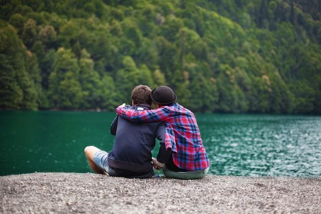 Jeune couple de voyageurs admirer un lac de montagne et prendre un selfie