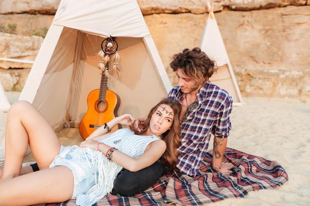 Jeune couple en wigwam sur la plage