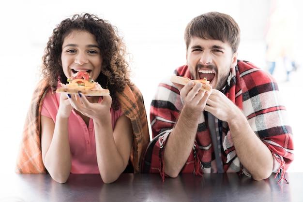 Jeune couple y a commandé deux pizzas savoureuses et les mange