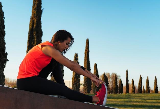 Jeune coureur femme qui s'étend de jambes avant de courir dans un parc.