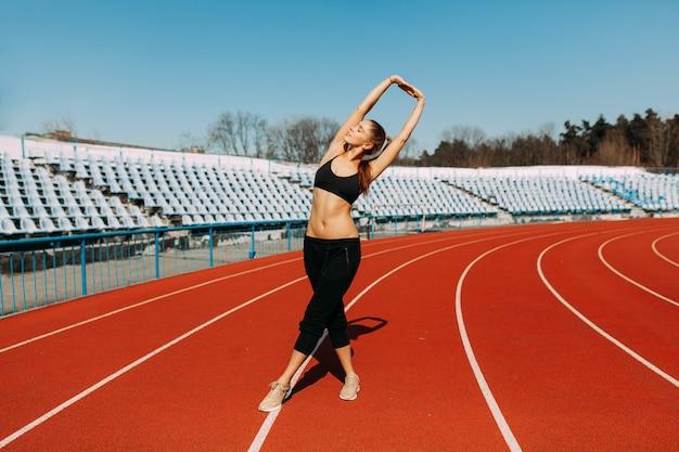 Jeune coureur de fitness femme se réchauffer avant de courir sur la bonne voie. exercices du matin en été