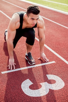 Jeune coureur masculin musclé sur la ligne de départ