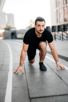 Jeune coureur masculin prenant la position prête à démarrer. concept de sport urbain. jogging matinal. homme athlétique en vêtements de sport noirs faisant de l'exercice. concept de mode de vie actif sportif.