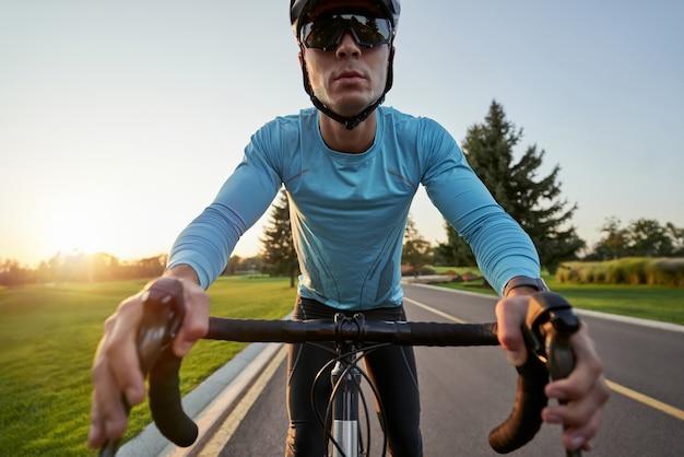 Jeune coureur masculin professionnel ciblé en vêtements de sport et casque de protection faisant du vélo à vélo dans