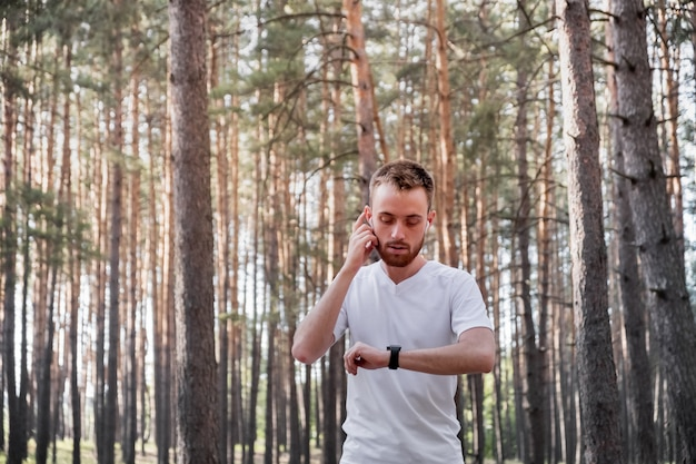 Jeune coureur masculin utilisant la technologie moderne au cours de l'exercice de jogging cross-country.