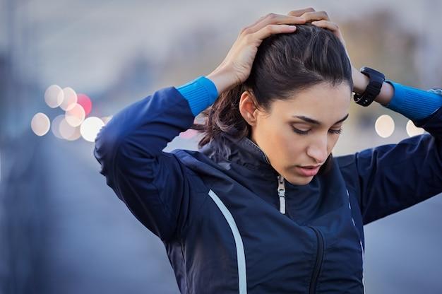 Jeune coureur prenant une pause de jogging tout en tenant la tête et en respirant à l'extérieur