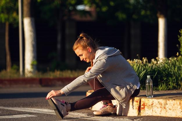 Jeune coureuse, athlète fait du jogging dans la rue de la ville au soleil.