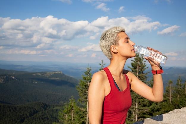 Jeune coureuse tenant une bouteille d'eau