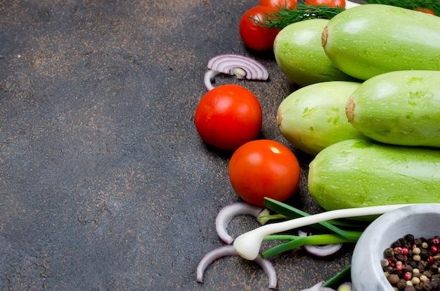 Jeune courgette, tomates, herbes et épices au printemps sur fond noir