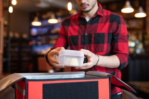 Jeune courrier de café mettant le conteneur avec de la nourriture dans un grand sac tout en emballant les commandes des clients avant de les livrer