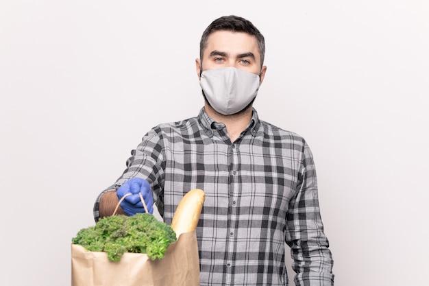 Jeune courrier en chemise décontractée et gants de protection et masque vous passant un sac en papier avec des produits alimentaires frais du supermarché