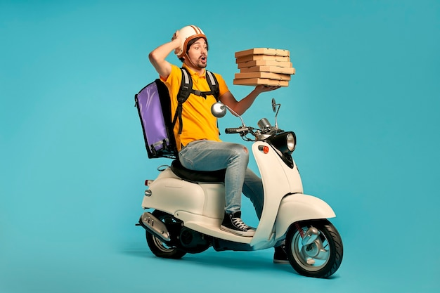 Jeune courrier, livreur de pizza en uniforme avec sac à dos thermo sur un cyclomoteur isolé. livraison express à domicile. commande en ligne.