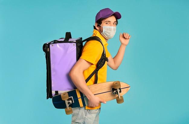 Jeune courrier, livreur en uniforme et masque avec sac à dos thermo et skate isolé. livraison rapide à domicile. commande en ligne pendant la pandémie de coronavirus covid-19.