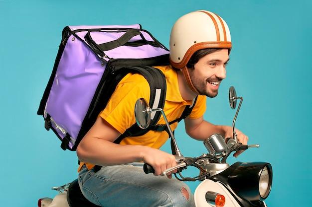 Jeune courrier, livreur en uniforme avec sac à dos thermo sur un cyclomoteur isolé. livraison express à domicile. commande en ligne.
