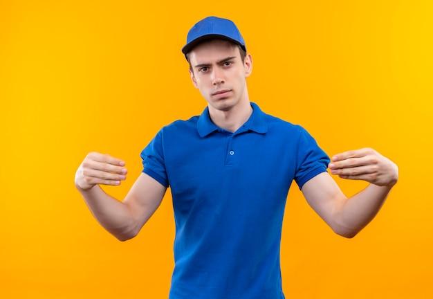 Jeune courrier portant l'uniforme bleu et bonnet bleu relie sérieusement ses doigts