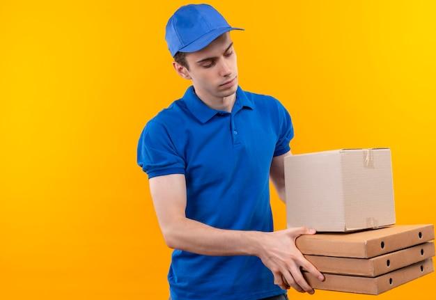 Jeune courrier portant l'uniforme bleu et casquette bleue détient des boîtes