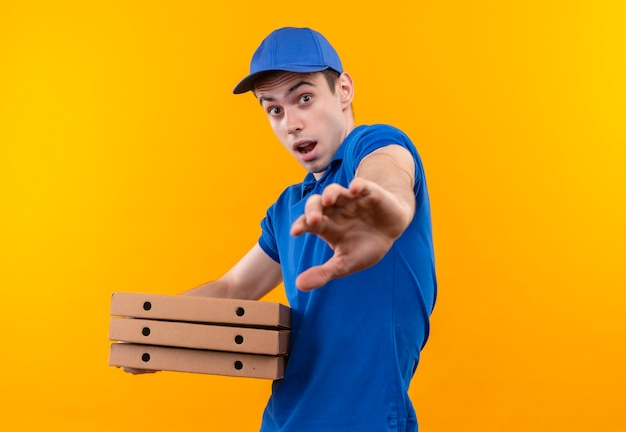 Jeune courrier portant l'uniforme bleu et casquette bleue faisant face effrayée détient des boîtes