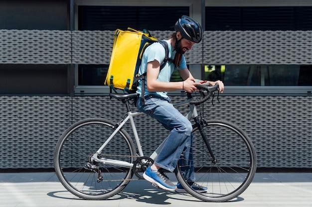 Jeune coursier barbu livrant de la nourriture sur un vélo, vérifiant la commande avec un téléphone intelligent. concept de service de livraison