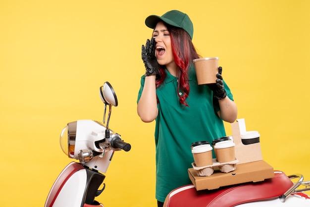 Jeune coursier féminin avec café et dessert sur jaune
