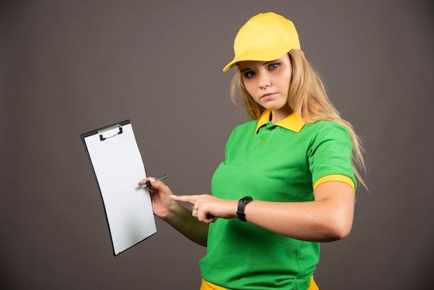 Jeune coursier féminin avec un crayon pointant sur le presse-papiers.