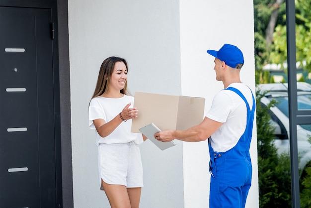 Jeune coursier livrant des marchandises à une jeune femme à la maison.