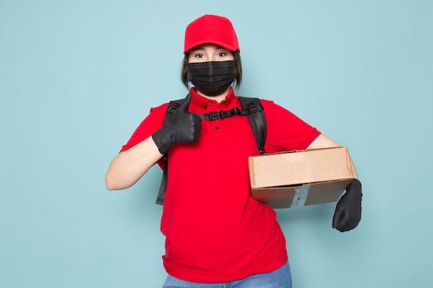 Jeune coursier en polo rouge casquette rouge masque de protection stérile noir sac à dos noir tenant le paquet sur bleu