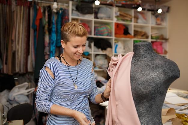 Jeune couturière attache le tissu au mannequin à l'aide d'aiguilles.