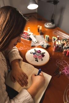 Jeune couturière la conception de nouveaux vêtements sur un ordinateur portable