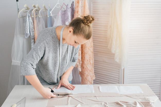 Jeune couturière fabrique des vêtements pour couper le tissu