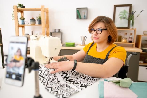 Jeune couturière handicapée en lunettes à l'aide d'une machine à coudre tout en donnant des cours en ligne sur la couture