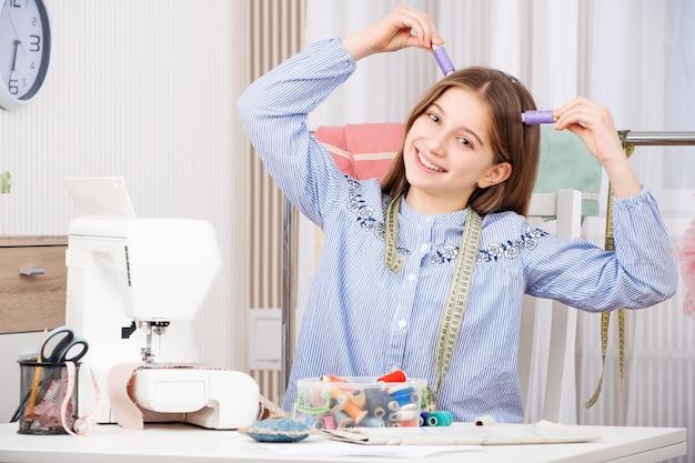Jeune couturière jouant avec des fils de bobines