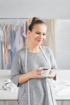 Jeune couturière une pause avec une tasse de thé