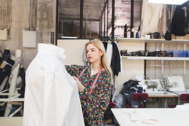 La jeune couturière porte des vêtements sur un mannequin.