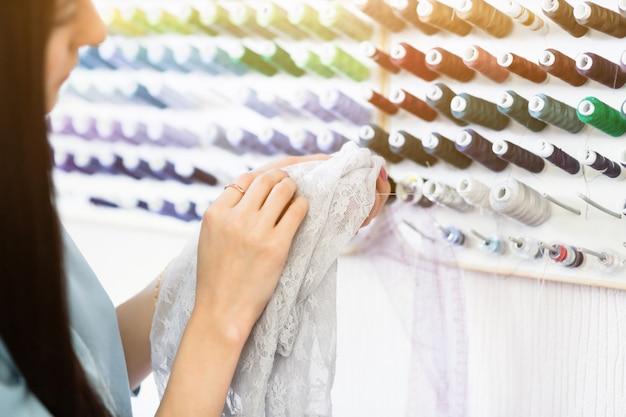 Jeune couturière sélectionne les fils pour confectionner de beaux vêtements à la mode.