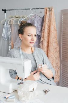 Jeune couturière travaillant sur machine à coudre
