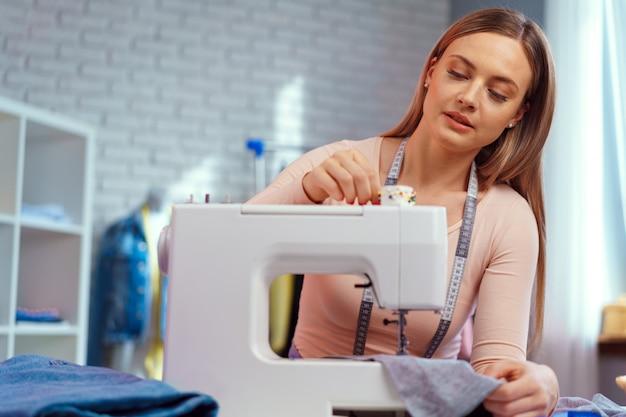Jeune couturière travaillant sur sa machine à coudre sur une usine textile