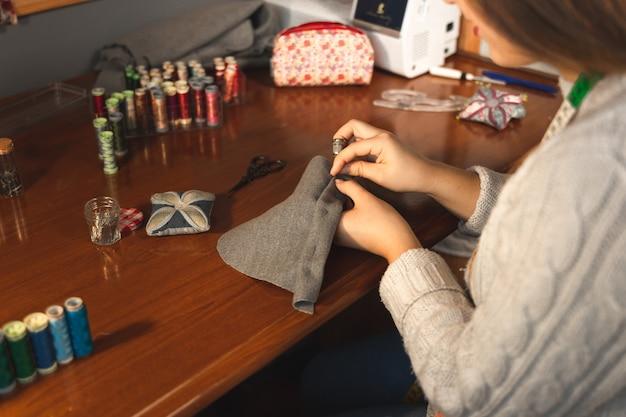 Jeune couturière travaillant sur le studio avec des textiles
