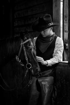 Jeune cow-boy et cheval dans l'écurie sur fond noir