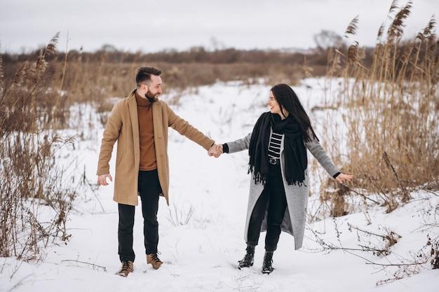 Jeune coyple ensemble dans un parc d'hiver