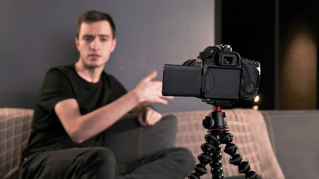 Jeune créateur de contenu parlant et faisant des gestes à l'homme se filmant à l'aide d'une caméra sur un trépied