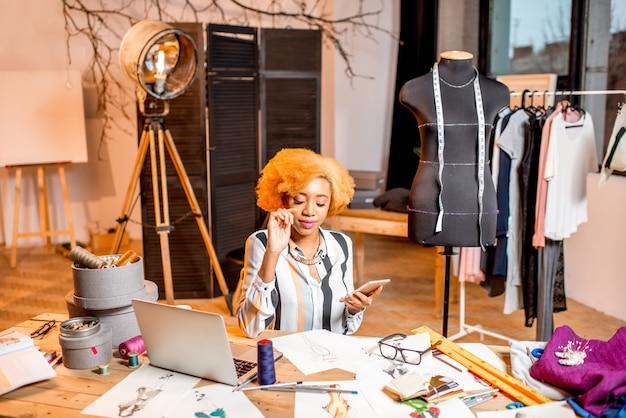 Jeune créateur de mode africain travaillant avec des dessins de vêtements et un ordinateur portable assis à l'intérieur du studio avec différents outils de couture