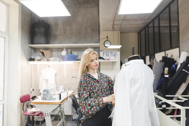 Jeune créateur de mode debout dans le studio et essayant des vêtements sur un mannequin.