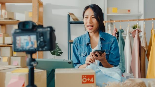 Jeune créateur de mode femme asiatique utilisant un téléphone mobile recevant un bon de commande et montrant des vêtements en streaming