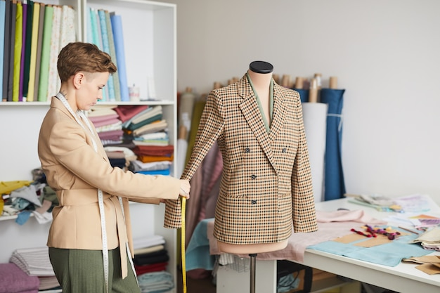 Jeune créateur de mode prenant des mesures de la veste avec un ruban à mesurer dans l'atelier
